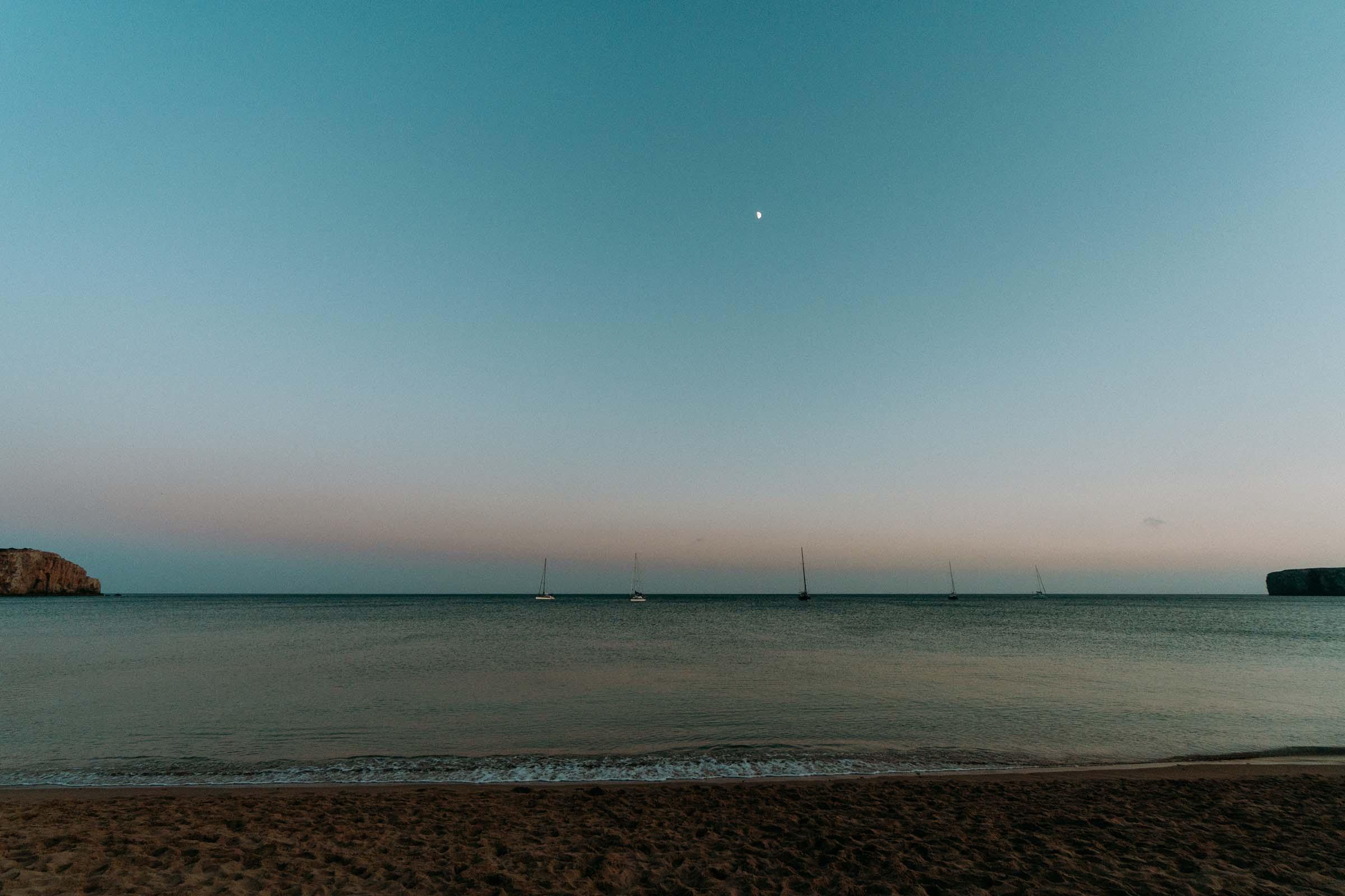 dusk at the beach with boats far away