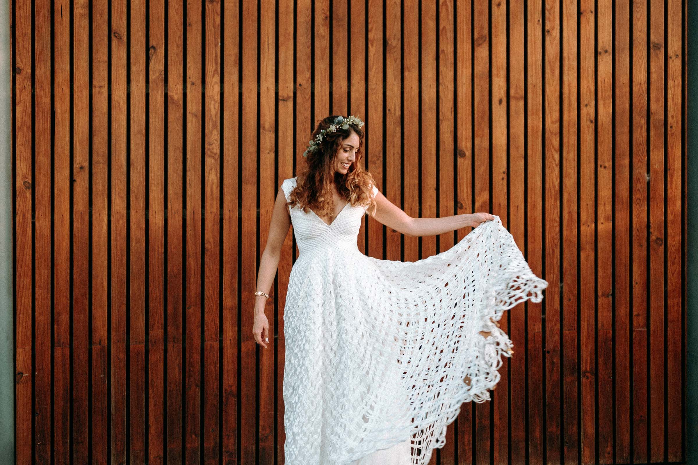 bride with alternative wedding dress against a wooden wall