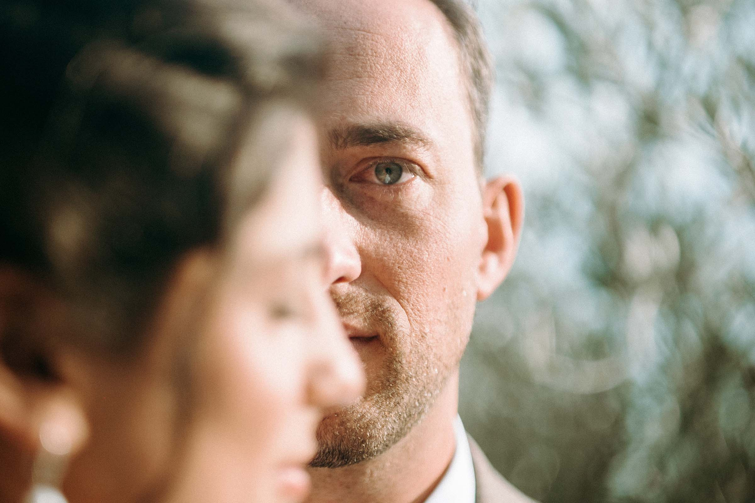 groom with green eyes staring straight into the camera with bride covering half of the face