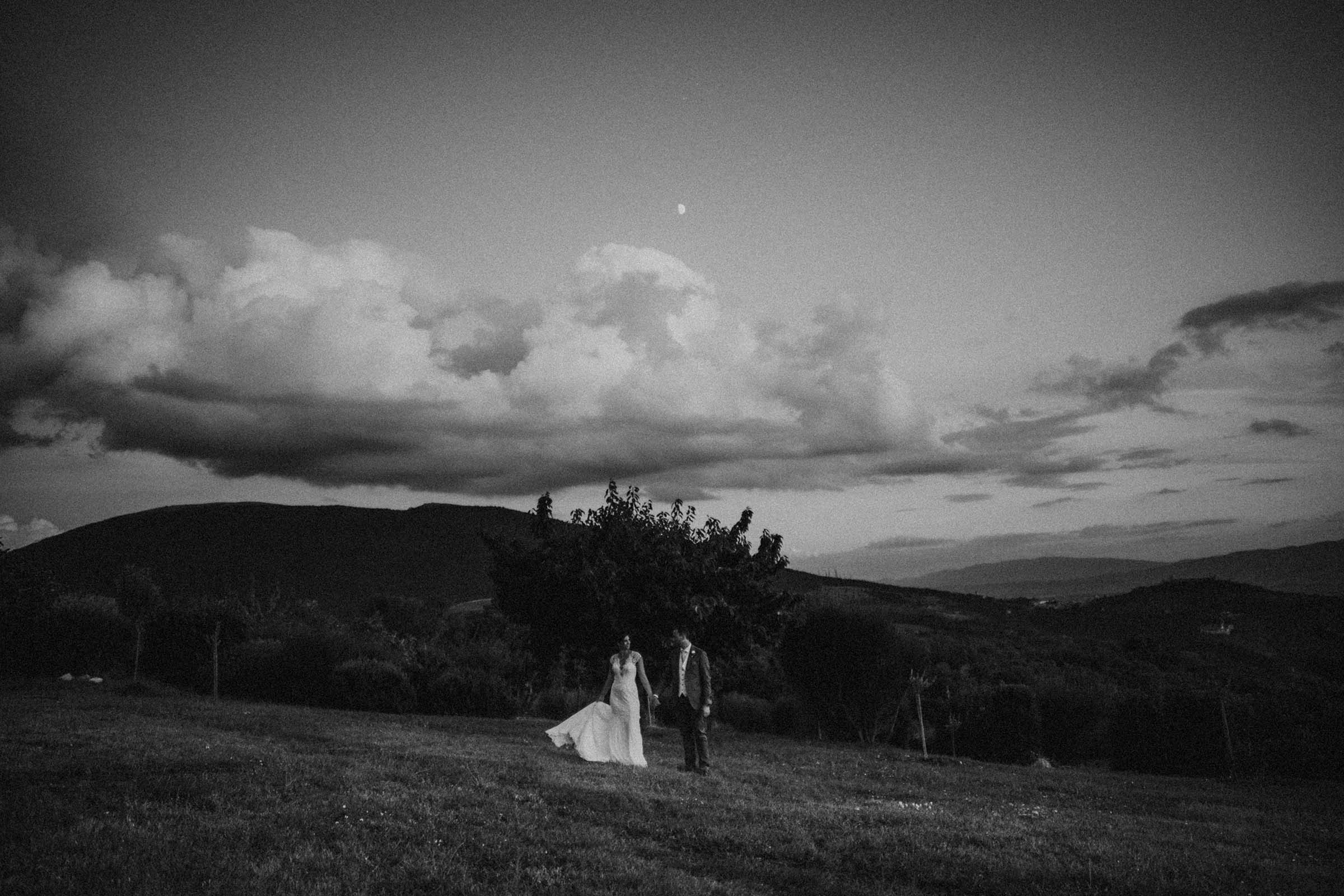 black and white photo if a couple and the moon above