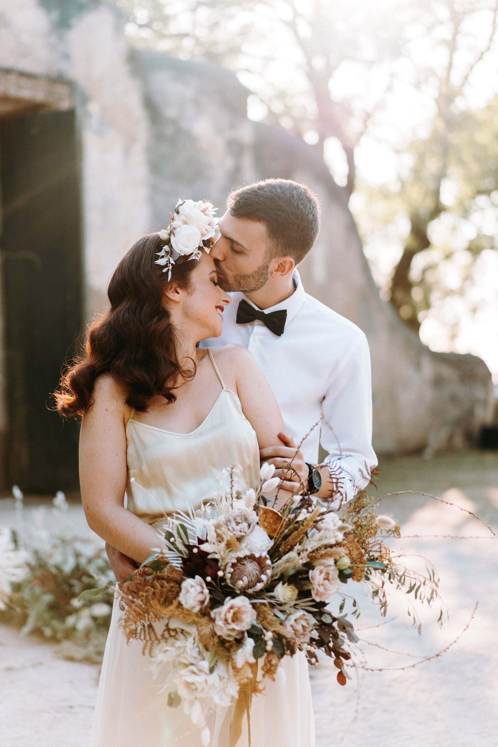 groom kissing brides forehead