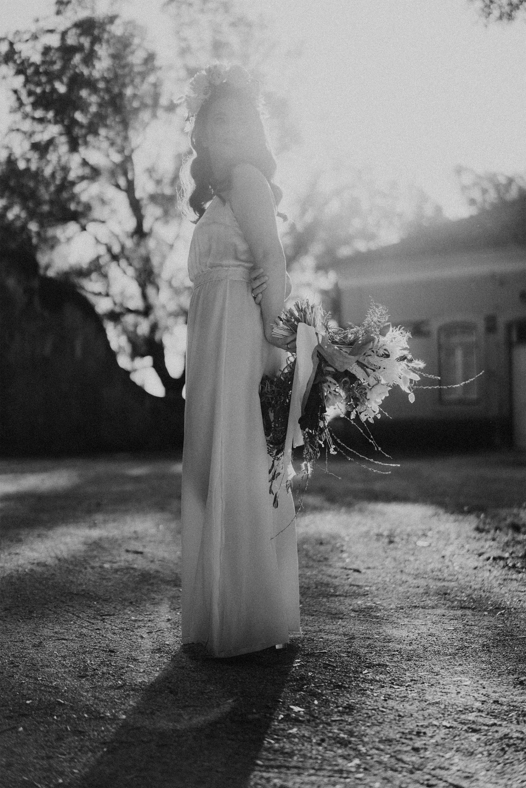 black and white photo of a bride holding her bouquet behind her back