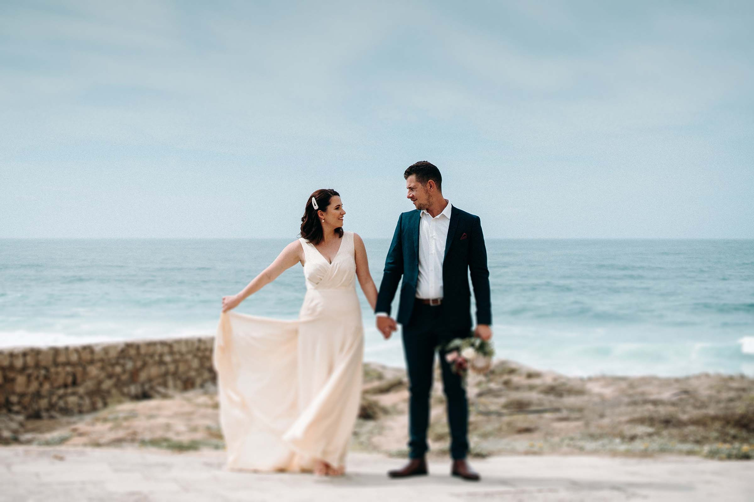 freelens photo of couple while bride holds her dress to the side