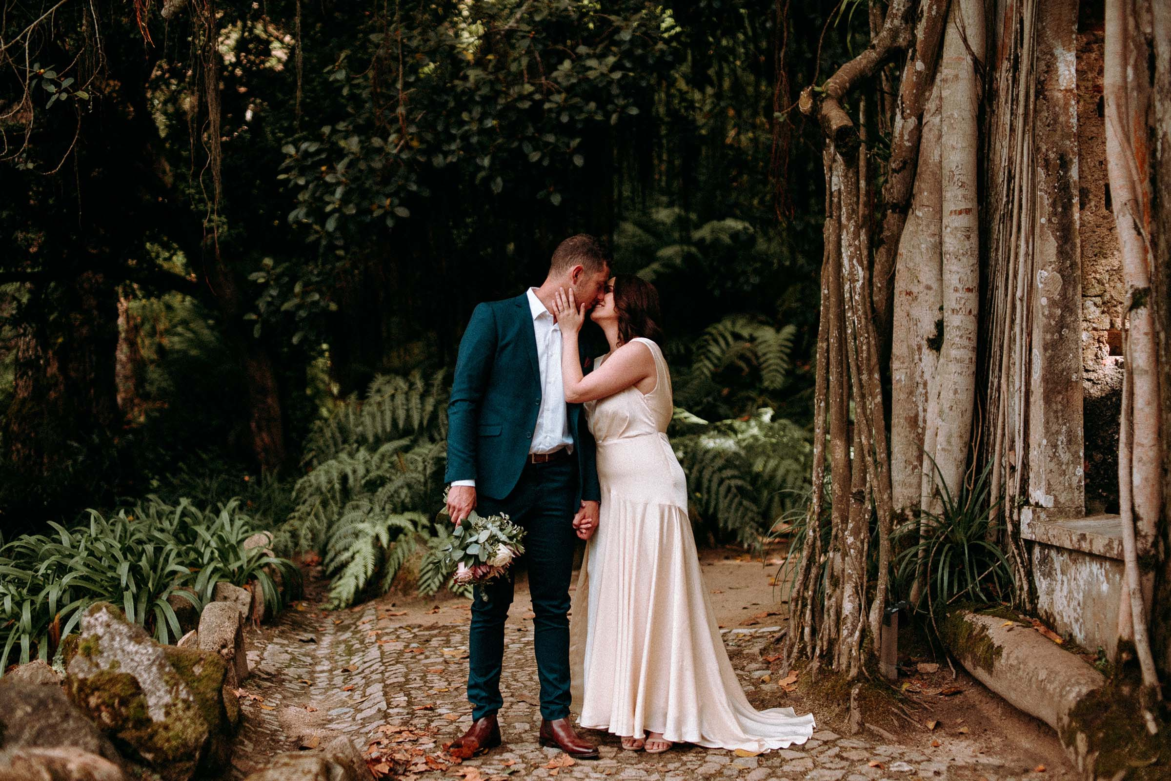 couple kissing in monserrate garden while groom hold bouquet