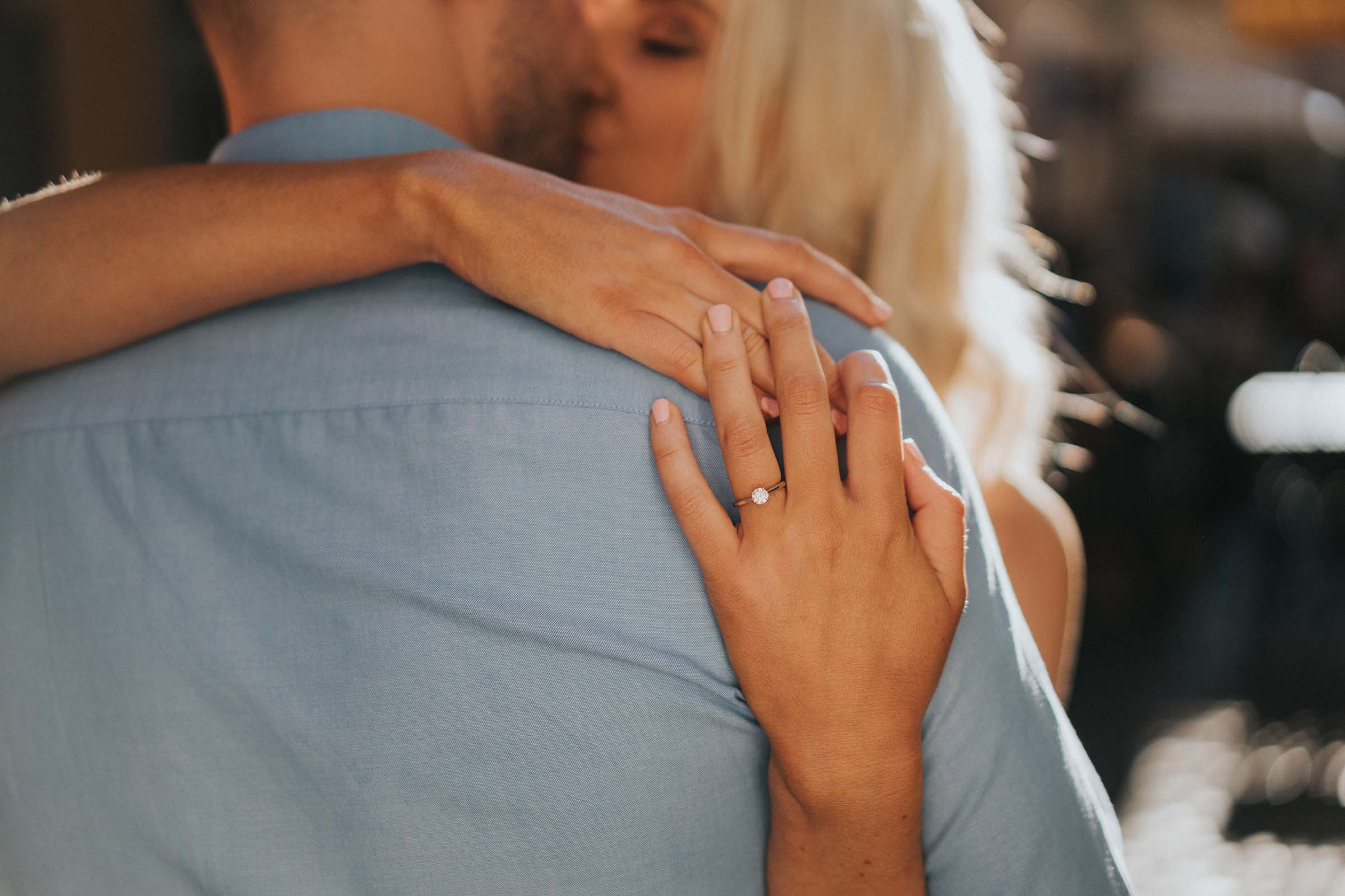 bride hugging groom with hands behind his back with engagement ring