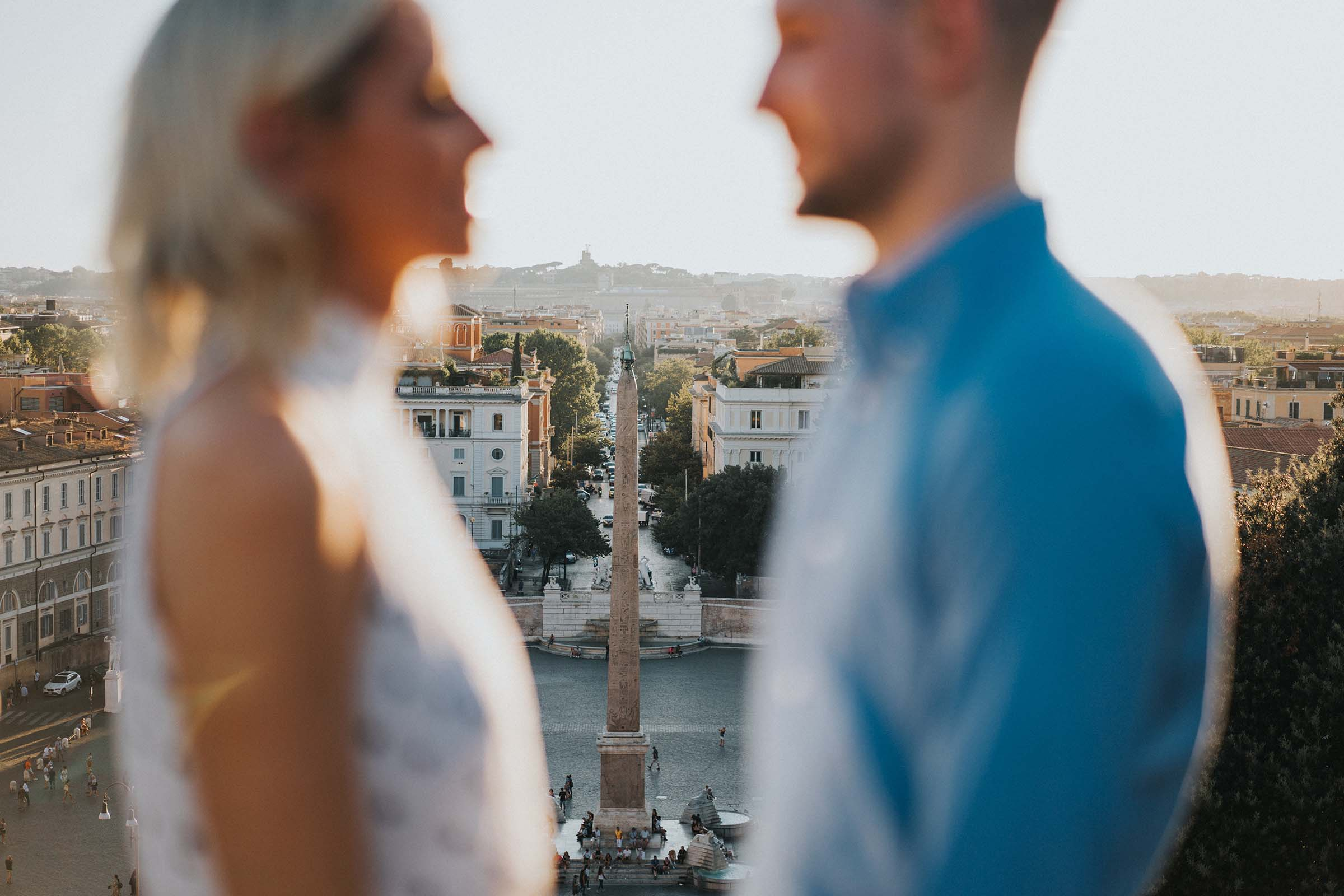 couple out of focus in foreground with obelisk behind them in Rome
