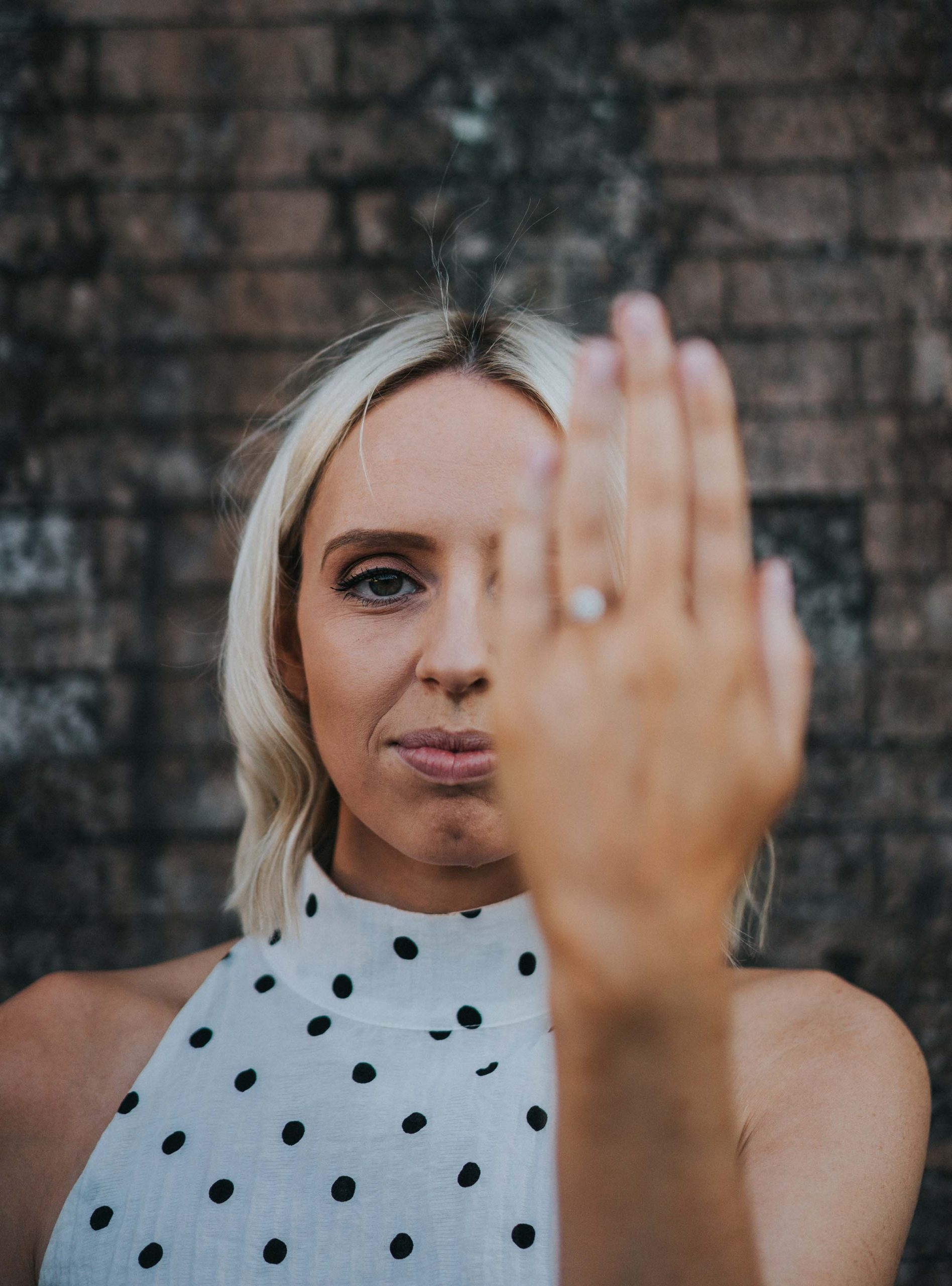 bride covering half of face with hand with engagement ring out of focus