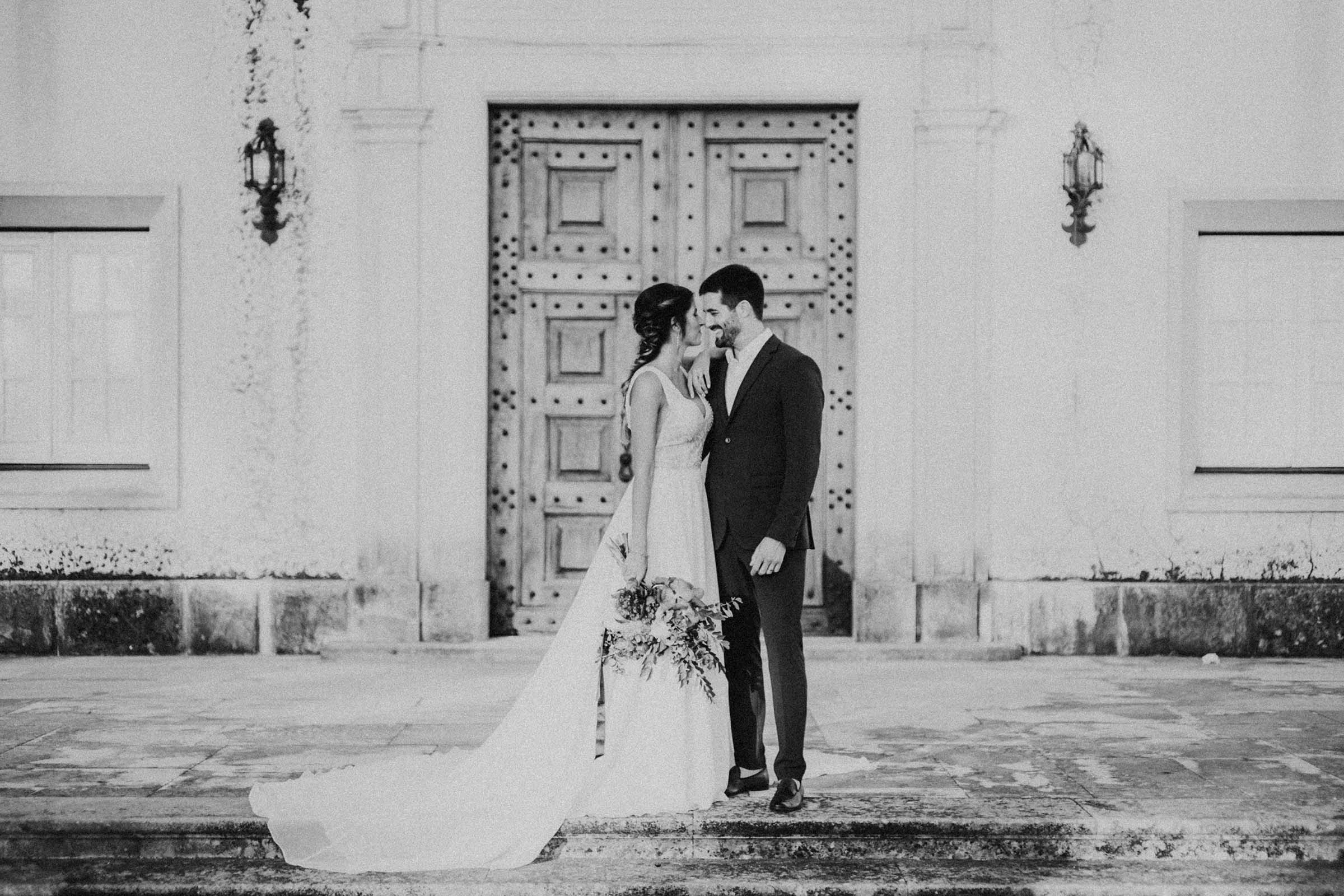 couple smiling in front of an oak door black and white