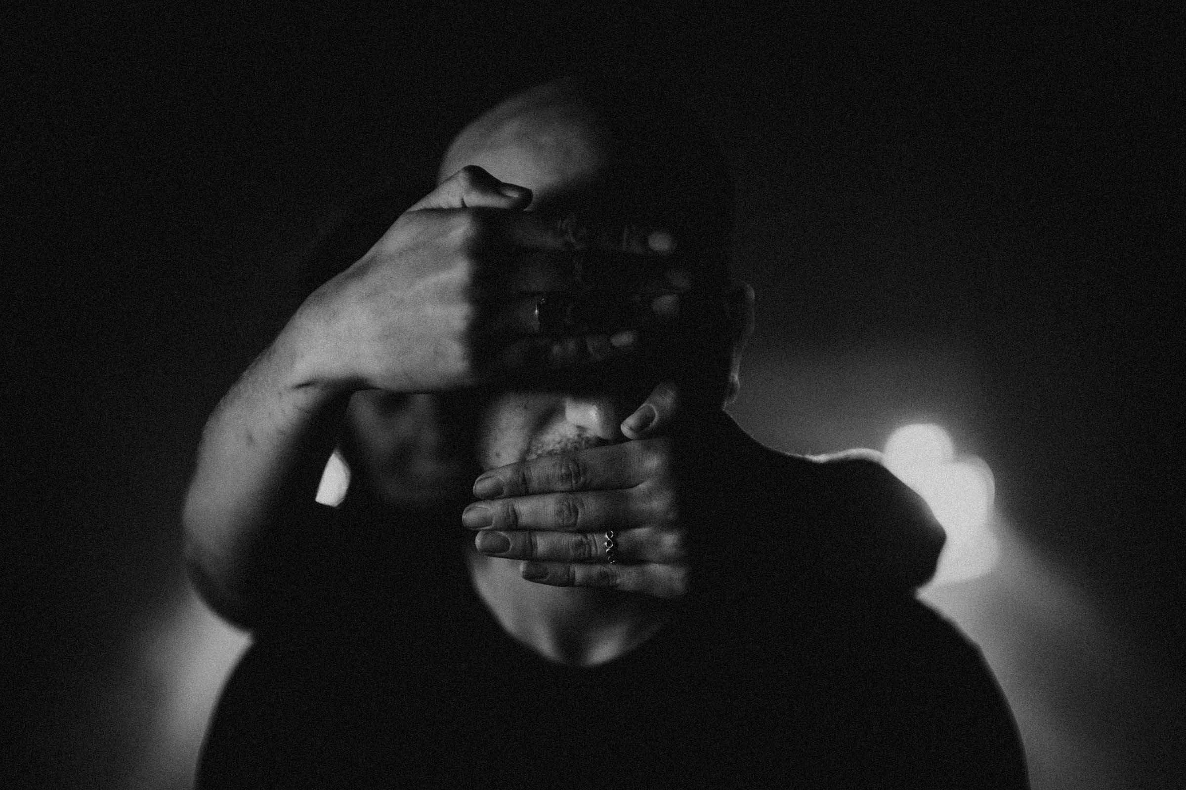 moody black and white photo grooms face covered by hands
