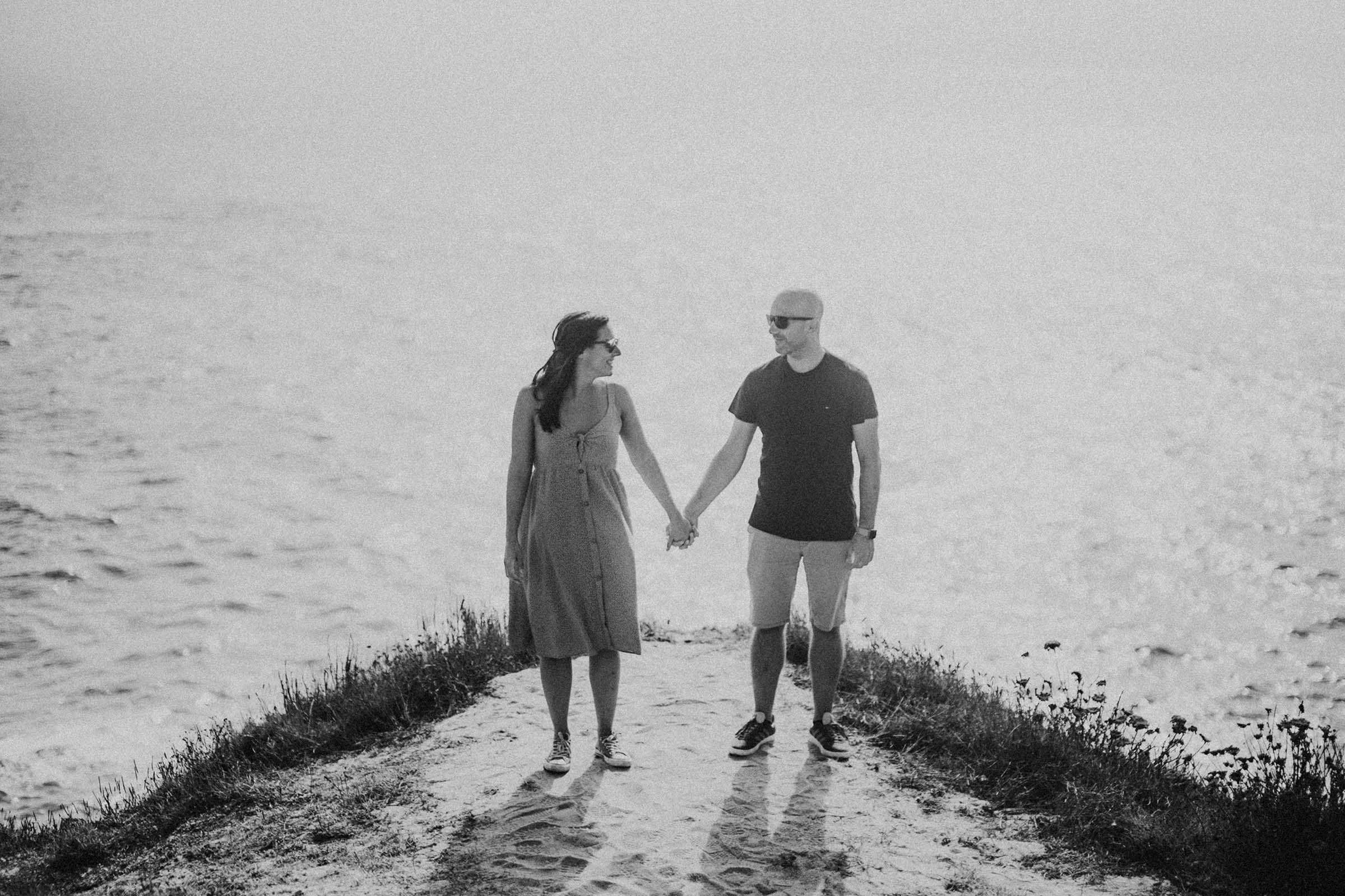 black and white photo holding hands on a cliff