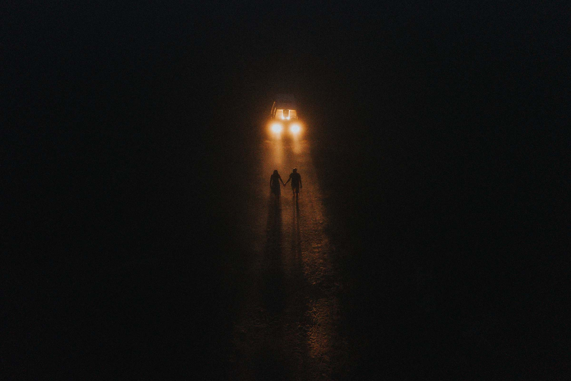 night photo couple walking away from the van headlights on