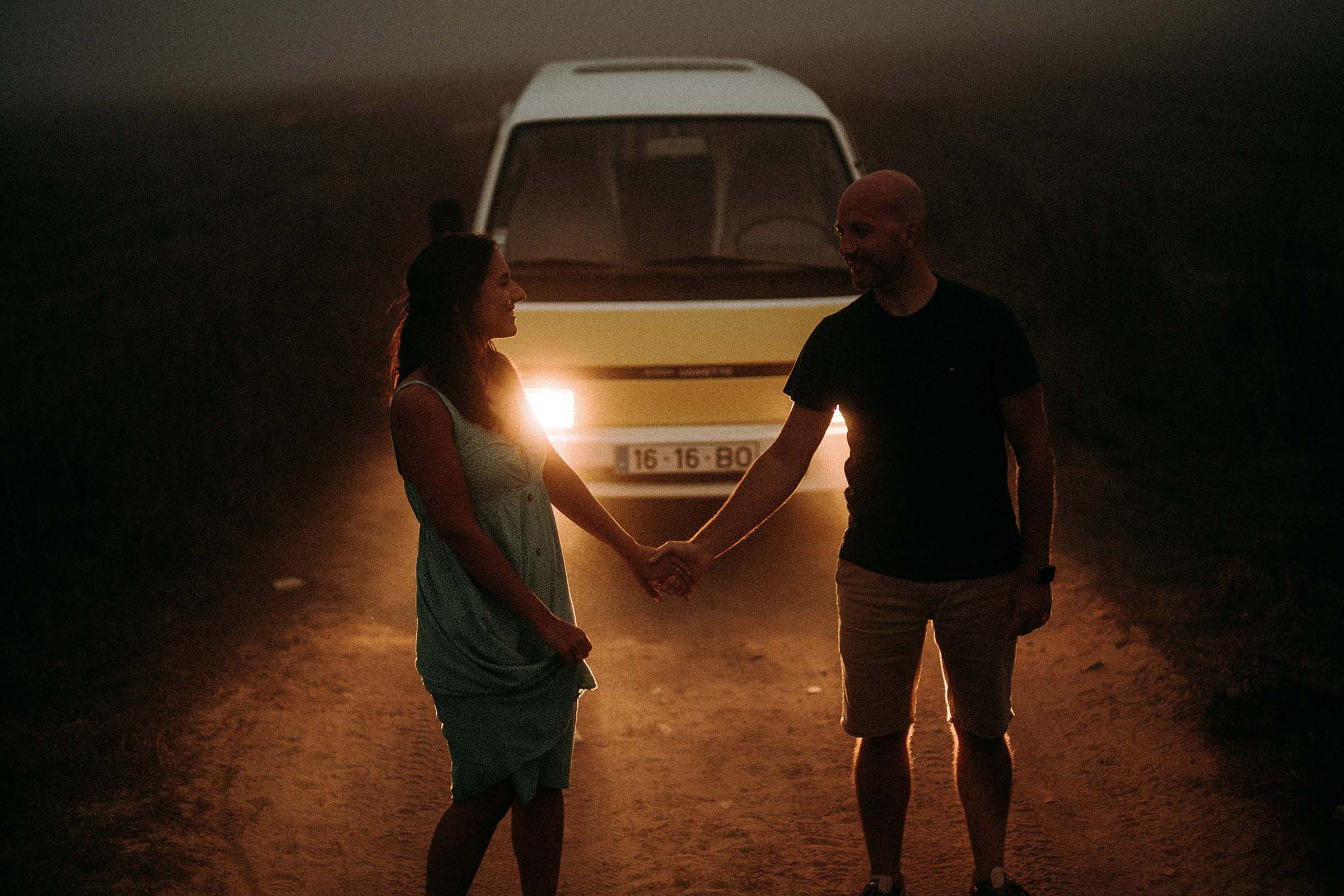 couple holding hands in front of van