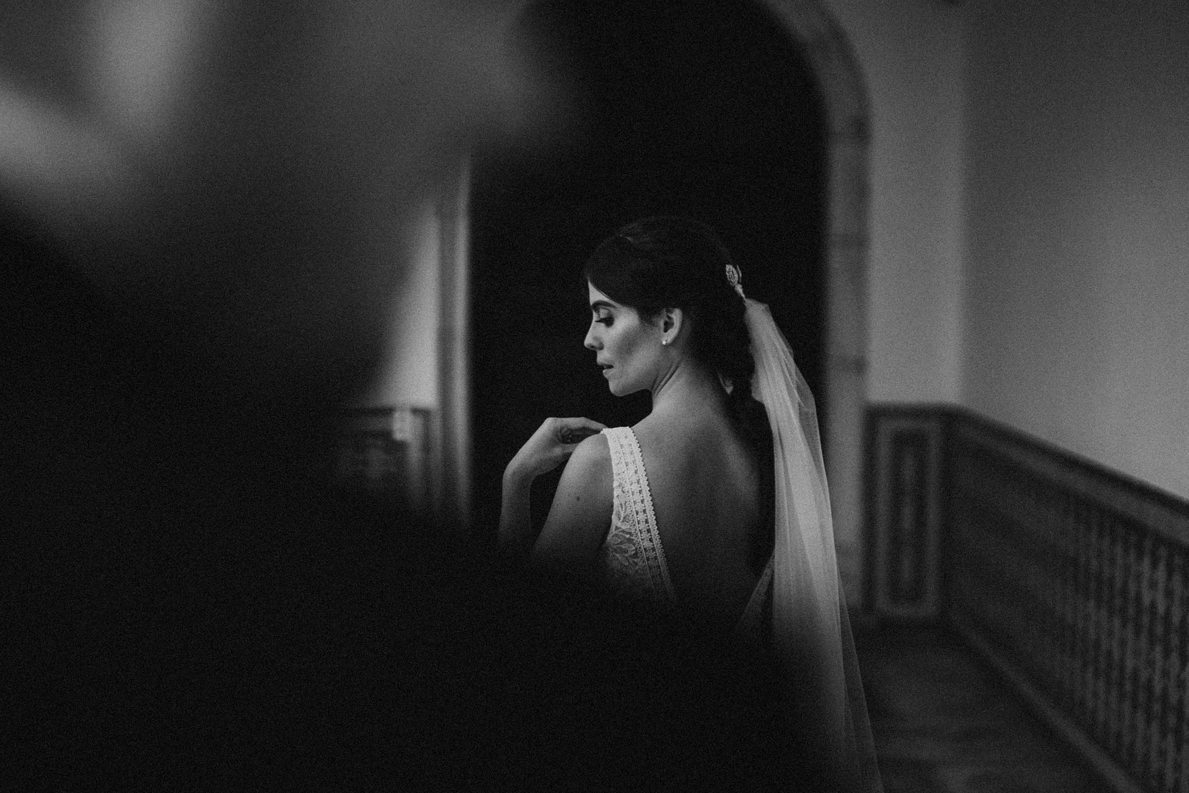 black and white photo bride touching her shoulder with groom in foreground out of focus